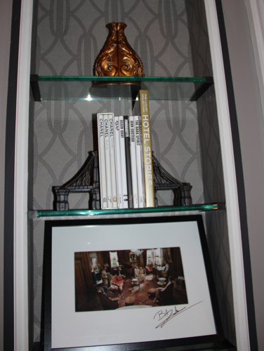 """These Brooklyn Bridge bookends are available at RH Restoration Hardware, and the books between them are available at The Shops at The Plaza. On the shelf below is a photo of """"The Great Gatsby"""" scene at The Plaza signed by Baz Luhrmann, and that isn't available anywhere."""