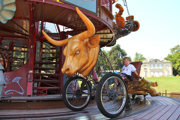 Bull riding Swiss-style? The toddler chose the bull on the Carrousel des Fables.